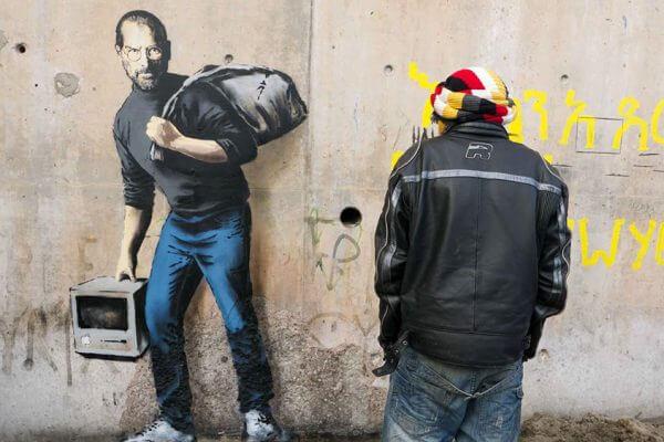 Banksy highlights the refugee crisis through Steve Jobs street art in Calais